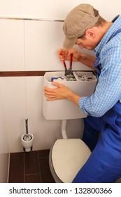 Young craftsman repairing Toilet