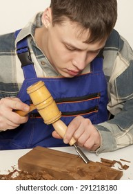 Young craftsman in uniform working at carpentry