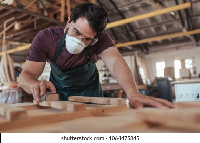 Young craftsman wearing a protective mask and glasses skillfully hand sanding pieces of a wooden furniture design while working in his large woodworking shop