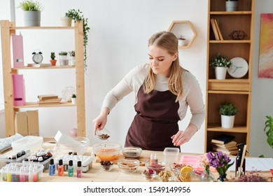 Young craftswoman adding grated dry spices into bowl with liquid soap mass with orange essence in studio