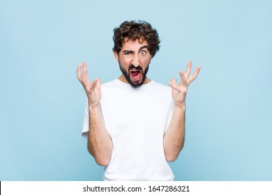 young crazy bearded man screaming with hands up in the air, feeling furious, frustrated, stressed and upset against flat wall