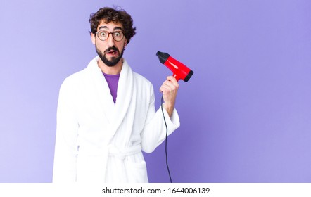 young crazy bearded man  wearing bathrobe with a hairdresser