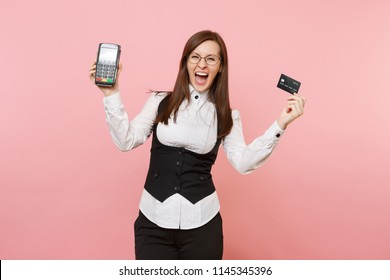 Young crazy business woman scream hold wireless modern bank payment terminal to process and acquire credit card payments, black card isolated on pink background. Lady boss. Achievement career wealth