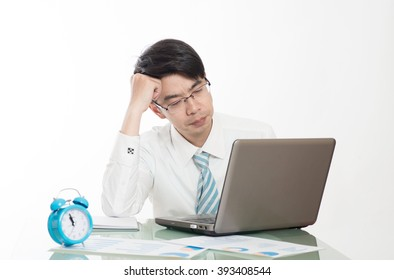 young crazy businessman punching switching off alarm clock sitting at office desk working with computer laptop in deadline project concept and business stress concept