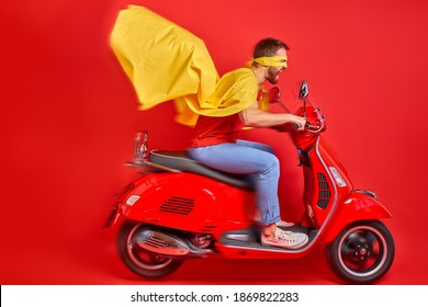 young crazy caucasian guy drive moped wearing cloak and mask rushing road party in super heroes role, isolated red color background