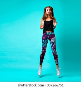 Young crazy hipster girl jumping and dancing, bright studio portrait , printed leggings and crop top, blue background.