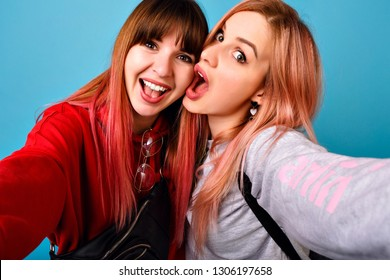 Young crazy hipster women making selfie at blue background, surprised funny emotions, long pink hairs, casual outfits.