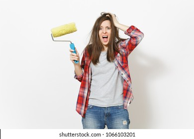 Young crazy loony woman in casual clothes holding paint roller for wall painting and clinging to head isolated on white background. Instruments for renovation apartment room. Repair home concept