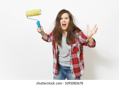 Young crazy loony woman in casual clothes holding paint roller for wall painting and screaming isolated on white background. Instruments, tools for renovation apartment room. Repair home concept
