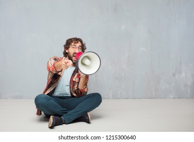young crazy mad man  fool pose with a megaphone. announcement concept