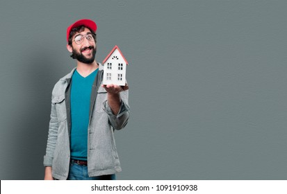 young crazy man with beard and red cap and a house model