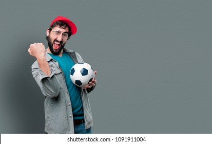 young crazy man with beard and red cap holding a soccer ball