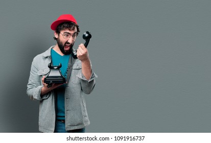 young crazy man with beard and red cap holding a vintage telephone