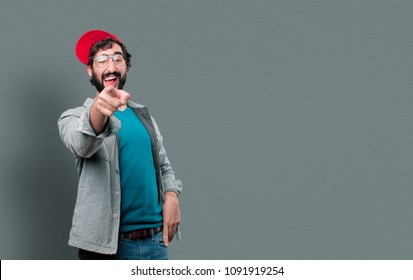 young crazy man with beard and red cap joking and pointing forward.