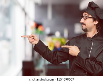 young crazy man as a chef smiling and pointing to the side with both hands, towards the place where the publicist may show a concept.