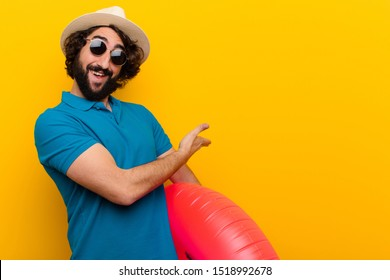 young crazy man feeling happy and cheerful, smiling and welcoming you, inviting you in with a friendly gesture against orange wall