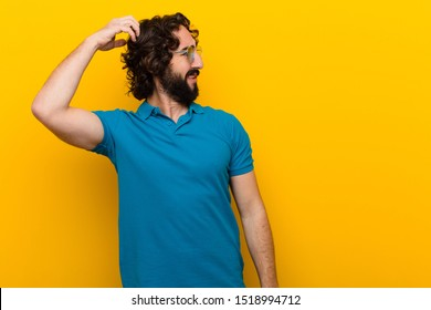 young crazy man feeling puzzled and confused, scratching head and looking to the side against orange wall