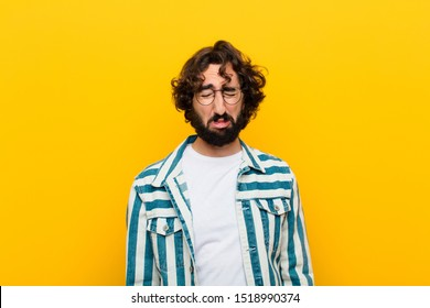 young crazy man feeling sad and whiney with an unhappy look, crying with a negative and frustrated attitude against yellow wall