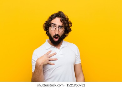 young crazy man feeling shocked, astonished and surprised, with hand on chest and open mouth, saying who, me? against yellow wall