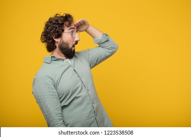 young crazy man looking far off into the distance, searching for a distant object with a confused look. Lateral or side view.