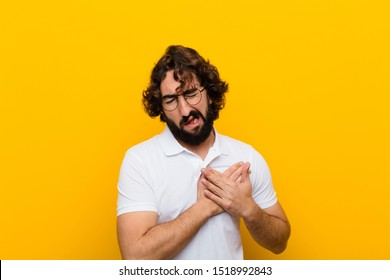 young crazy man looking sad, hurt and heartbroken, holding both hands close to heart, crying and feeling depressed against yellow wall