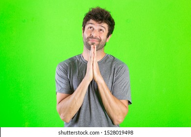 Young crazy man praying, sad expression over green background