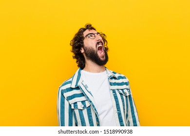 young crazy man screaming furiously, shouting aggressively, looking stressed and angry against yellow wall