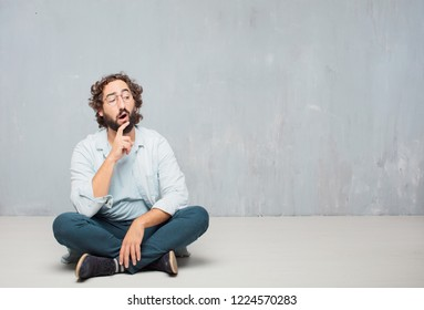 young crazy man sitting. with a goofy, dumb, silly look, feeling shocked and confused at a recent realization, not really understanding an idea.