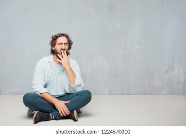 young crazy man sitting. Looking unenthusiastic and bored, listening to something dull and tedious, yawning in utter boredom.