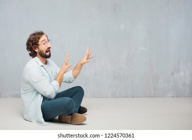 young crazy man sitting. looking scared, frightened and horrified, screaming in terror, facing doom, feeling very afraid. Lateral or side view.