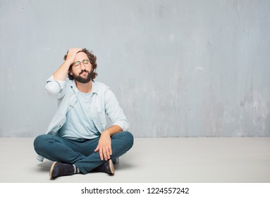 young crazy man sitting. with a sad look of disappointment and defeat, looking depressed and despaired, hopeless and in misery.