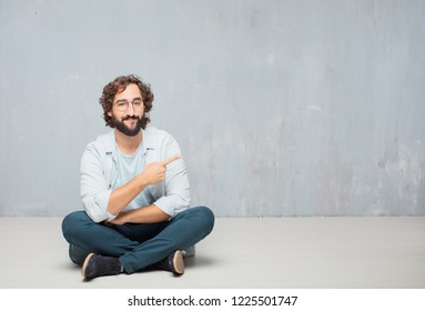 young crazy man sitting. smiling and pointing to the side with both hands, towards the place where the publicist may show a concept.