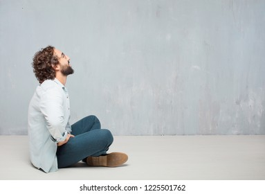 young crazy man sitting. smiling and looking up and sideways, towards the sky or to the spot where the publicist may place a concept or message.
