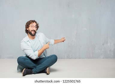 young crazy man sitting. smiling and pointing upwards with both hands, towards the place where the publicist may show a concept.