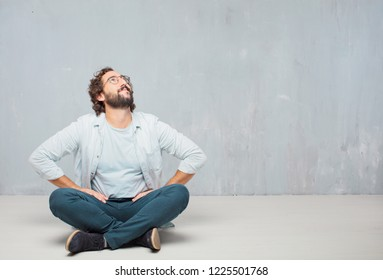 young crazy man sitting. smiling and looking upwards, towards the sky or to the spot where the publicist may place a concept or message.