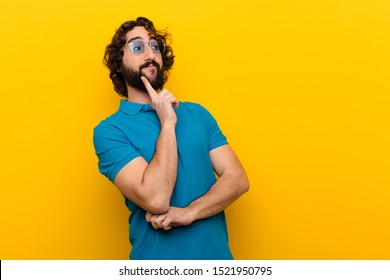 young crazy man smiling happily and daydreaming or doubting, looking to the side against orange wall