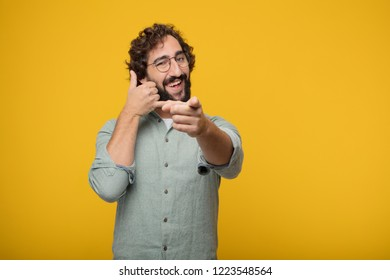 young crazy man smiling with a proud, satisfied and happy look, making a gesture as if accepting a challenge, confident of success.