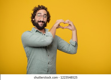 young crazy man standing sideways, smiling, looking happy and in love, making the shape of a heart with hands. Side or lateral view.