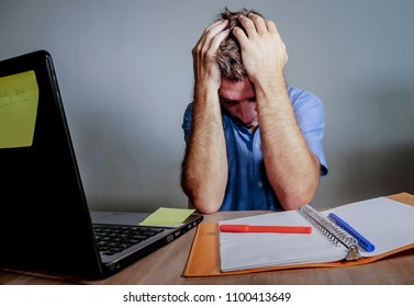 young crazy stressed and overwhelmed man working messy at office desk desperate with laptop computer covering face with hands frustrated in business work problem lifestyle concept