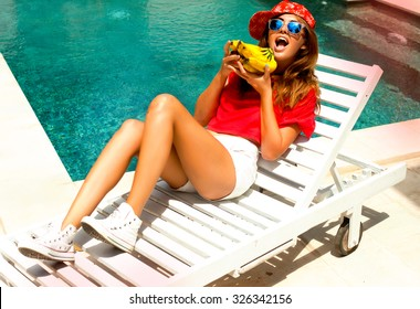 Young crazy teen girl laying and relaxed near pool at summer holiday nice hot day,crazy of her bananas,crop top,white shirts,swagger cap,listening music at big headphones.toned body,diet conception