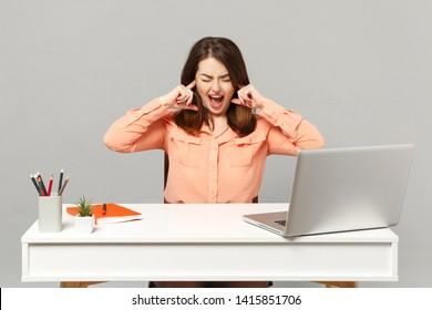 Young crazy woman screaming keeping eyes closed covering ears with fingers work at desk with pc laptop isolated on gray background. Achievement business career lifestyle concept. Mock up copy space