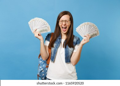 Young crazy woman student in glasses with backpack with closed eyes screaming hold bundle lots of dollars, cash money isolated on blue background. Education in high school university college concept