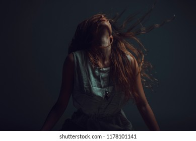 Young crazy woman throwing her hair around, expressing agony and pain