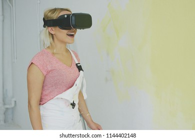 Young creative blond female in white jumpsuit enjoying with open mouth virtual reality in goggles headset standing at half-painted yellow wall