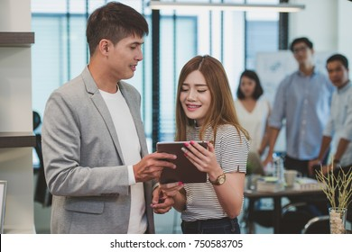 Young creative businessman holding digital tablet with female colleagues in background.