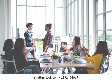 Young creative design asian team happy warm welcome to new cowork employee in meeting or training at office. Happy asian workplace in small business or startup in millennials concept with soft tone.