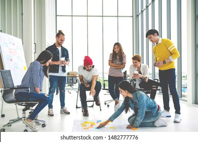 Young creative diverse group meeting and looking at project plan lay out on floor discuss or brainstorm business strategy with post note. Workshop for startup team in modern office. Happy workplace.