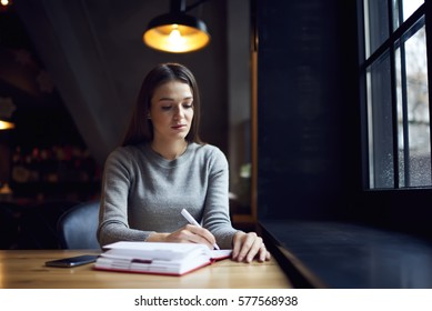 Young creative female author looking ways to get inspired in frosty rainy day sitting in warm cozy coffee shop continue work on her composition writing down ideas into notebook waiting for phone call