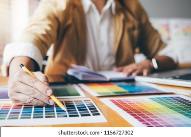 Young creative Graphic designer using graphics tablet to choosing Color swatch samples chart for selection coloring with work tools and accessories at workplace.