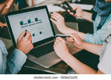 Young creative managers analyzing financial charts and graphs on a laptop. Successful teamwork and business brainstorm concept. Toned image